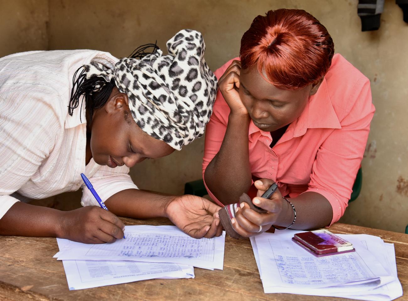Two female coffee farmers completing paperwork in Kenya