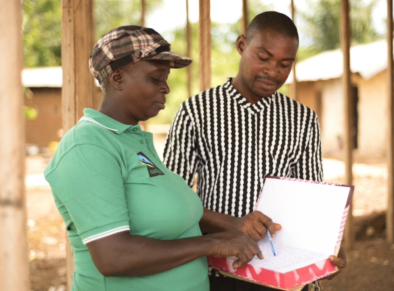 Two members of the Mfama cocoa co-operative in Ghana reading a document