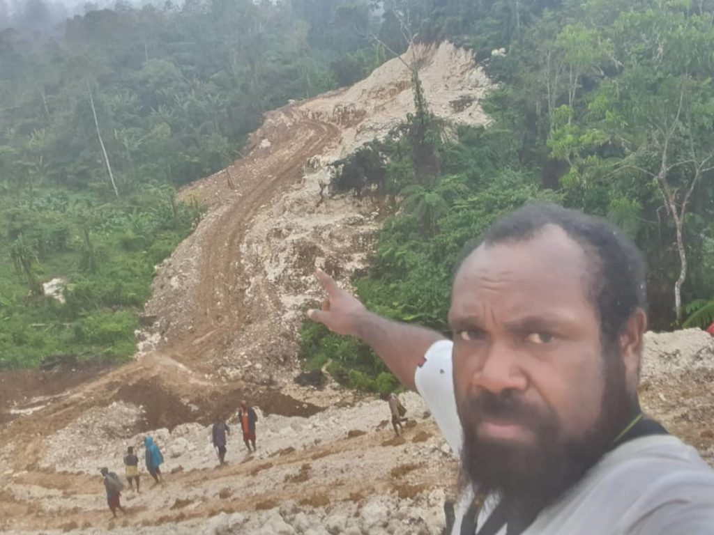 PNG coffee farmer points to road