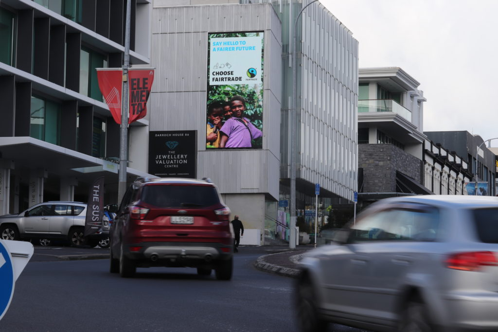 Image of buildings with billboard, cars in foreground